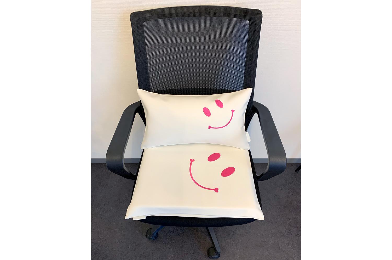 高級感溢れる白のフェイクレザーにとっても愛らしくキュートなピンクでスマイル『ニコフェイス』刺繍されたクッションセット